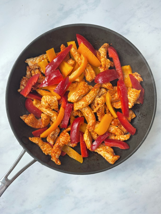 turkey strips in a frying pan with red and orange peppers