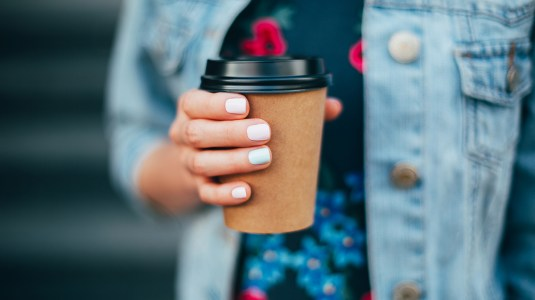 hand with paper cup of coffee take away