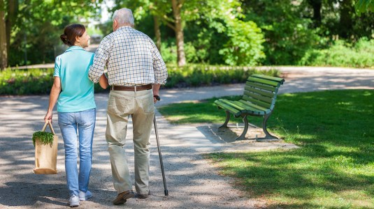A person supporting a senior while walking outdoors in the park