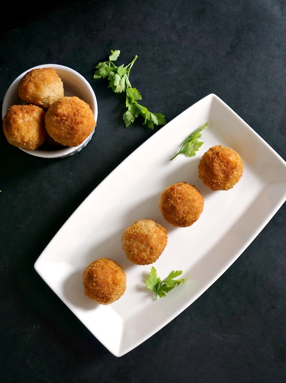 overhead view of 4 butter squash risotto balls on a white serving plate with a white bowl of risotto balls next to it and a sprig of parsley on a black background