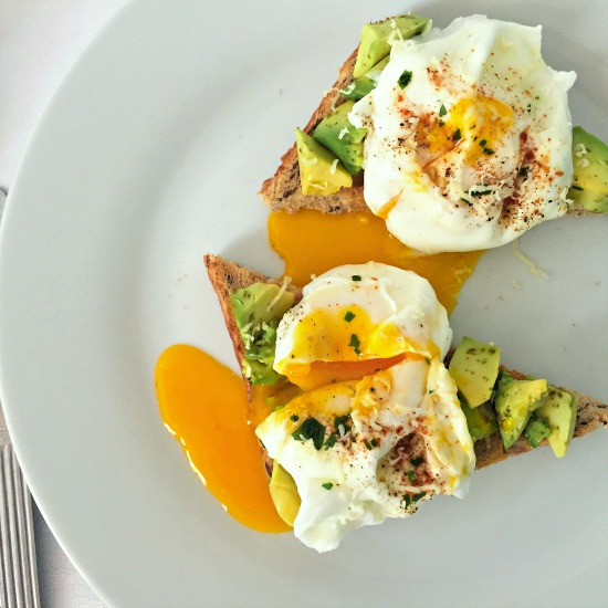 Poached egg avocado toast, a super healthy breakfast, served with a good pinch of black pepper.