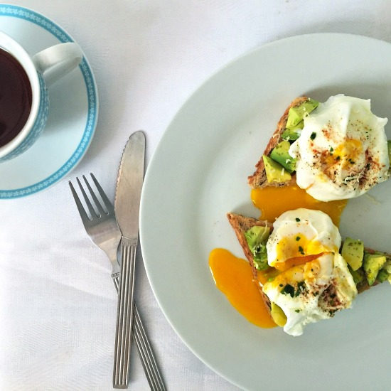 Poached egg avocado toast served with a nice cup of tea for a healthy start of your day.