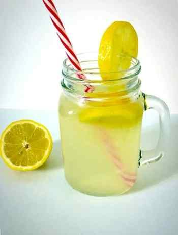 A mason jar of honey-sweetened lemonade with half a lemon next to it