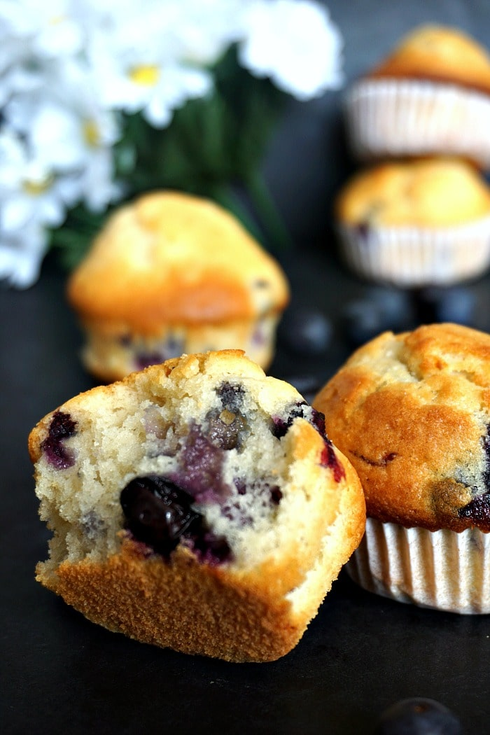 A halved fluffy bueberry muffin with other muffins around it