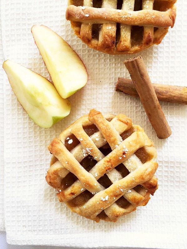 Overhead shot of two mini apple pies on a white background with 2 cinnamon sticks and two wedges of apples next to them