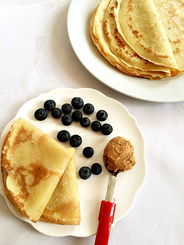 Perfect French crêpes recipe, served with blueberries and peanut butter. A super healthy breakfast.