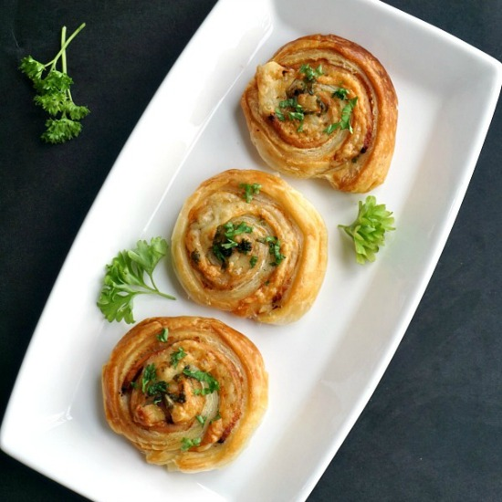 Overhead shot of a white plate with 3 puff pastry pinwheels with ham and cheese with parsley leaves scattered around