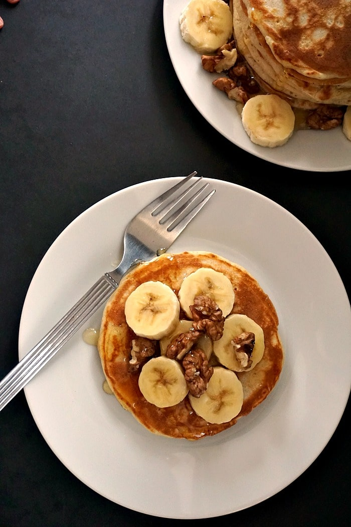 Overhead shot of a white plate with an American pancake that is topped with sliced bananas and walnuts and a fork next to it, and another plate of a stack of pancakes