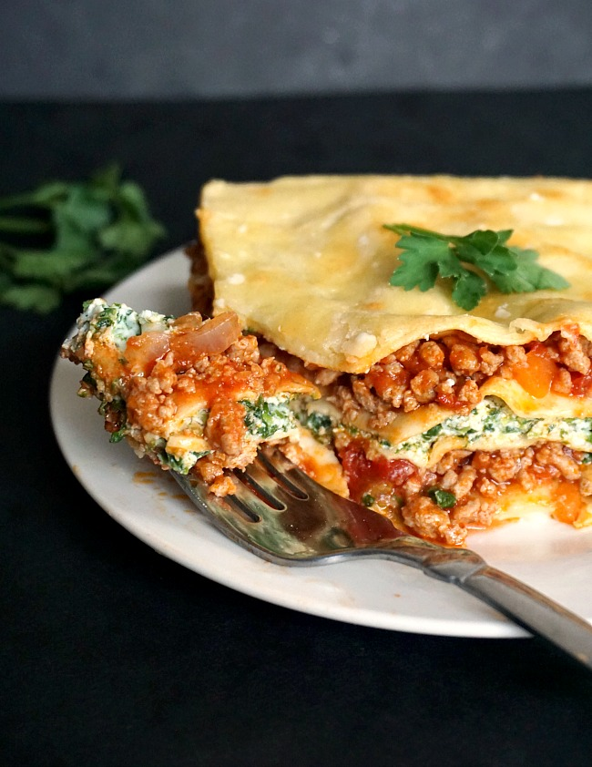 Close-up shot of a white plate with turkey spinach lasagna and a fork next to it