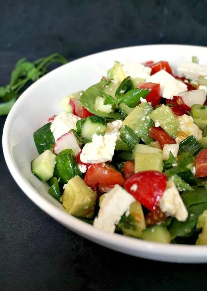 A white bowl of cucumber tomato avocado feta salad