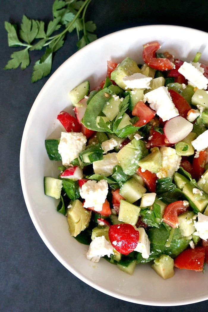 Overhead shot of half a plate of cucumber tomato avocado feta salad with a parley sprig next to it