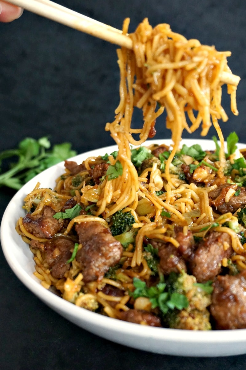 A white bowl of broccoli and beef stir fry with chopsticks grabing some noodles of the plate