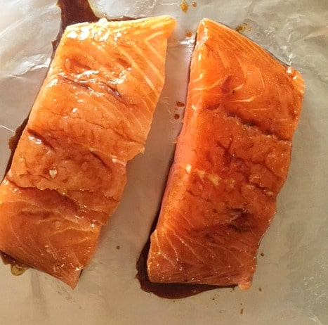 2 uncooked salmon fillets with teriaki sauce drizzled over them
