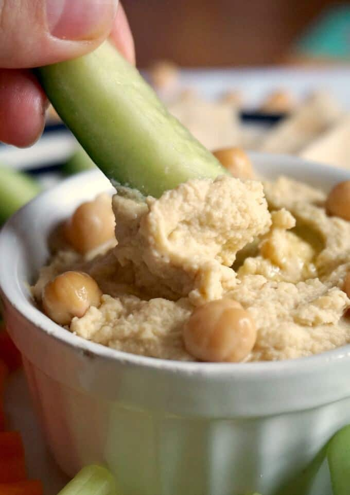 Cucumber stick dipped into a white bowl of spicy hummus