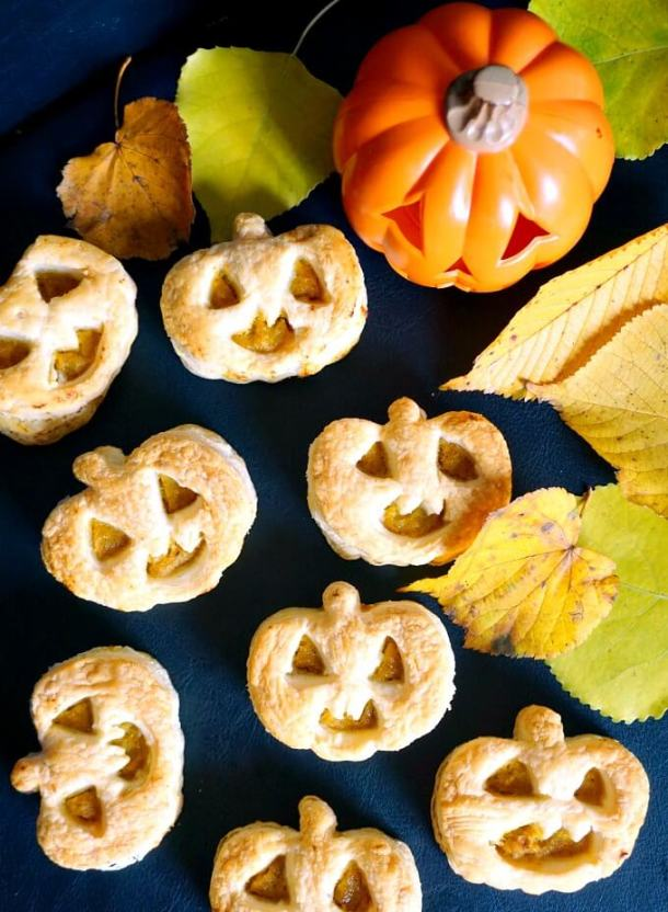 Overhead shoot of 7 Jack-O'-Lantern Pumpkin Hand Pies, a pumpkin and leaves on a black table top Easy Halloween Treats for School
