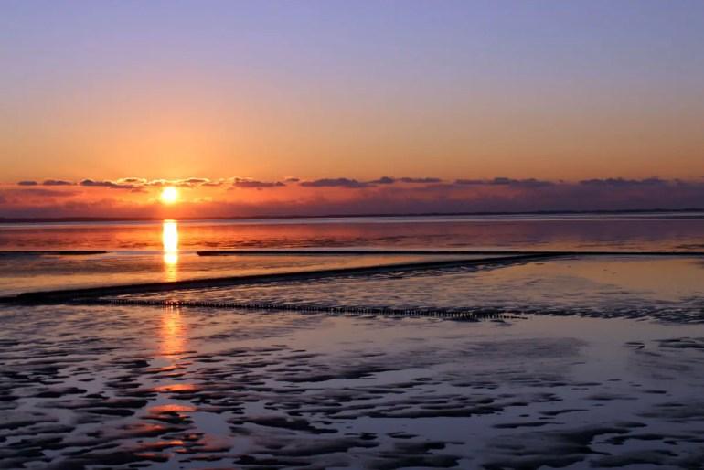 Tschüss Insel: Sonnenuntergang über dem Watt am Hindenburgdamm