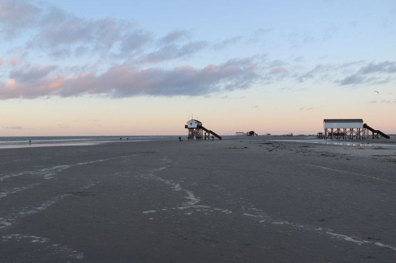 Abendstimmung am Strand, am Horizont die Pfahlbauten
