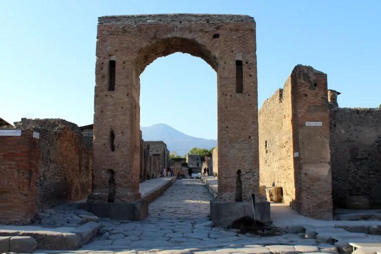 Vorne ein Torbogen, hinten der Vesuv