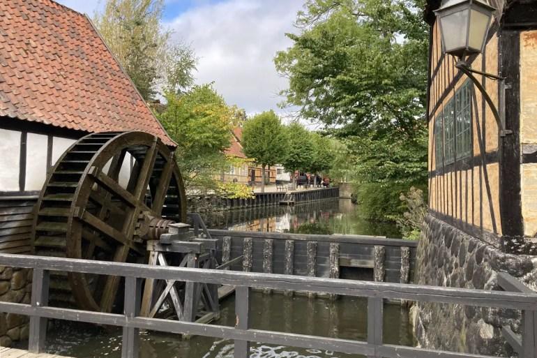 Ein kleiner Dorfteich mit Mühle im Einblicke in die Wohnwelt der 70er gibt's im Den Gamle By