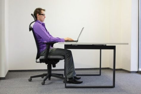 correct sitting position at workstation. man on chair working wi