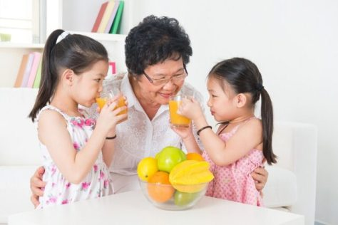 Asian family drinking orange juice. Happy Asian grandparent and