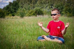 Young boy meditating in a field.