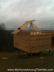 Securing the rafters in place for our small cabin