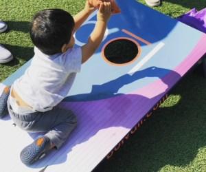 Baby playing cornhole