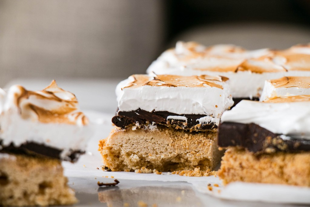 S'mores Blondies are the perfect treat! A layer of graham cracker blondies, chocolate ganache, and marshmallow fluff.