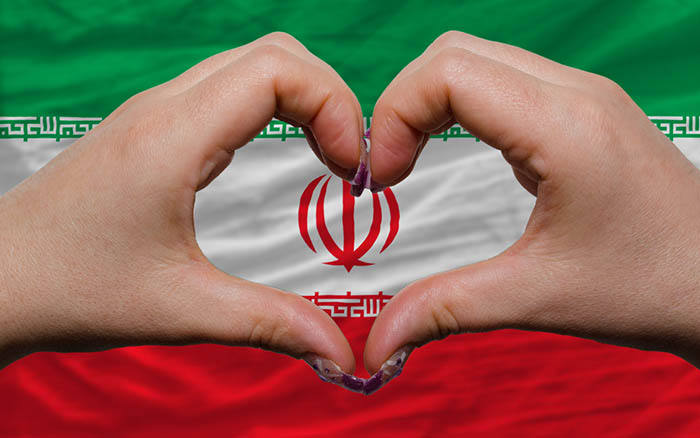 Gesture made by hands showing symbol of heart and love over national iran flag