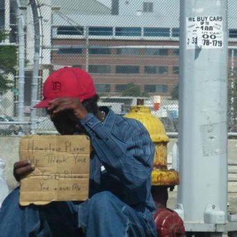 Homeless shields himself from the camera's stare