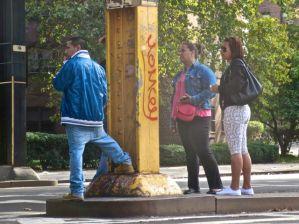 Pedestrians wait for bus (228 & Broadway).