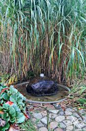 Ein Springbrunnen aus einem Stein in den Gärten der Welt.