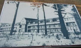 Das Bild der Informationstafel zeigt das Gebäude der Chirurgie der Beelitz-Heilstätten