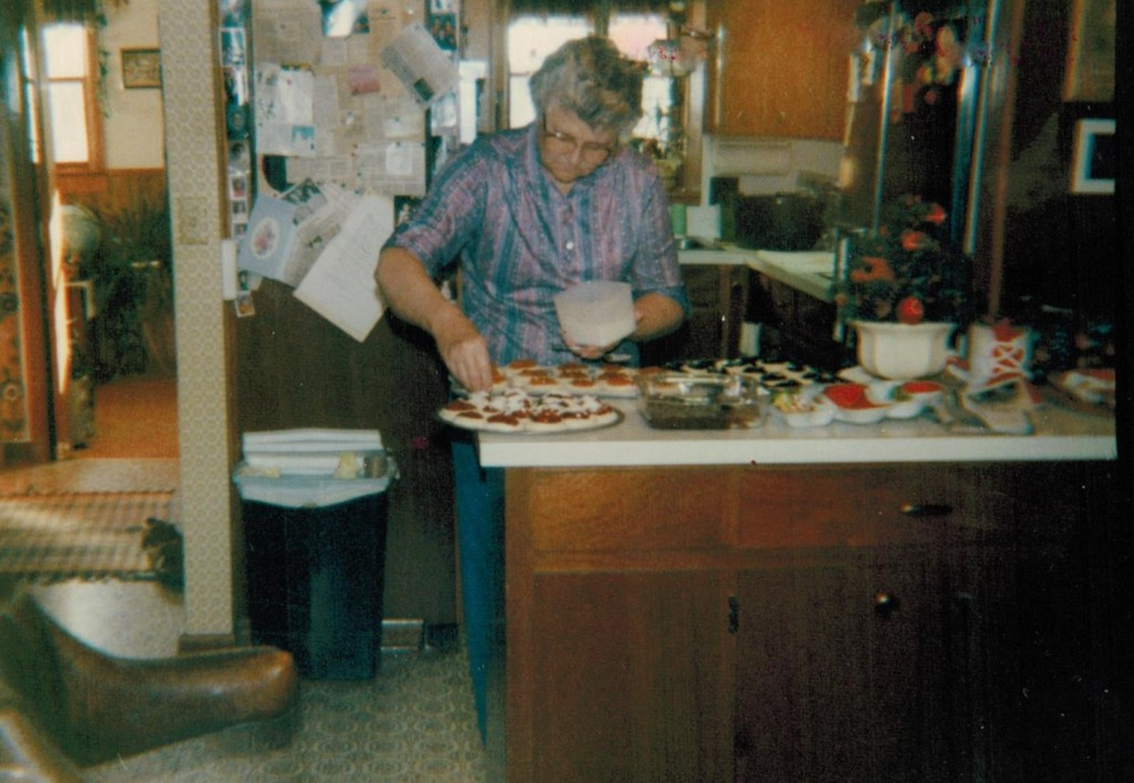 Mother in kitchen sprinkling kolaches
