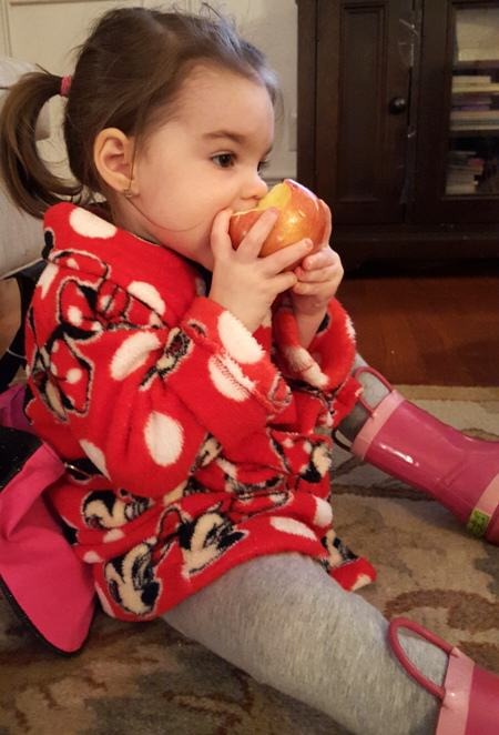 eating her apple in her robe and rain boots