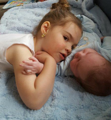 Riley giving baby brother a hug