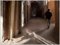 A man walking along a narrow arched street behind the Masjid-e-Jāmeh mosque in Yazd, Iran.
