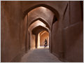 A youngster on a bicyce navigating through narrow mud-brick alley in the old part of Yazd city, Iran.