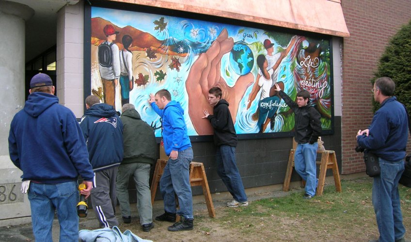 Students, community volunteers, building and grounds staff install exterior mural and pediment.