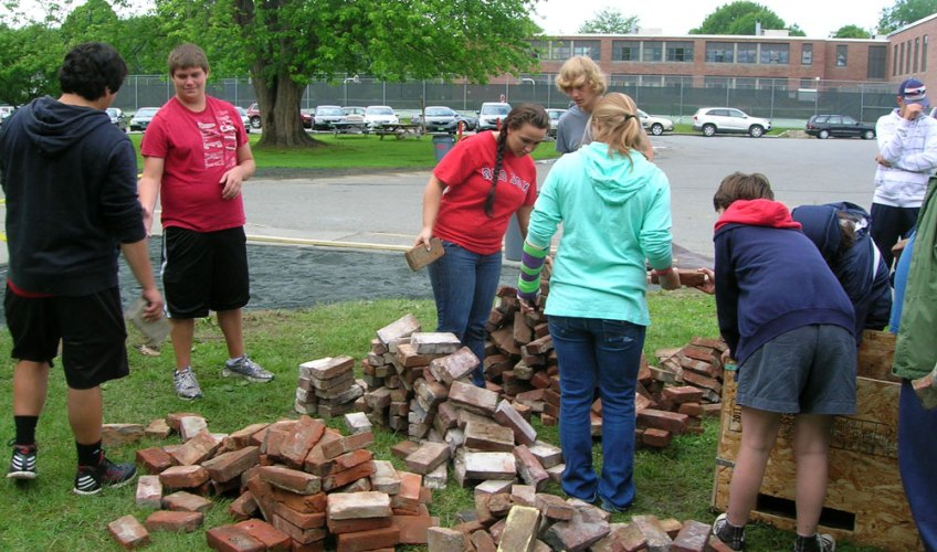 Students and staff prepare a Pompeii style brick.