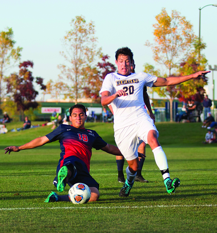 Metro midfielder Arturo Vega slides for the ball in the 3-1 win against Regis Oct. 16 at Regis University Athletic Field as they extend their winning streak to four games. Photo by Brandon N. Sanchez • bsanch36@msudenver.edu