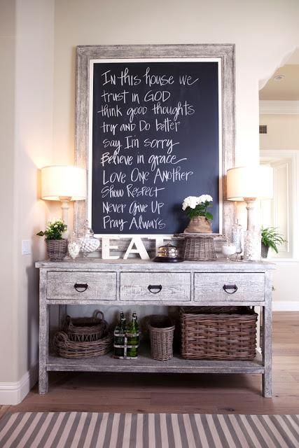 Rustic entrance table with large chalkboard above.