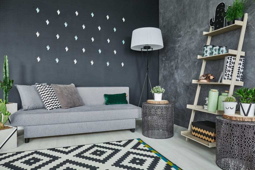 Room with black cactus wall decor and sofa