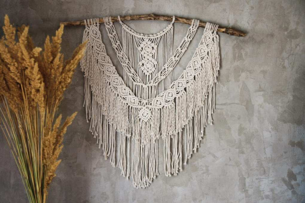 Wall panel in the style of Boho made of cotton threads in natural color using the macrame technique for home decor and wedding decoration. Beautiful boho macrame wall panel will add a cozy atmosphere and charm to any space in your home