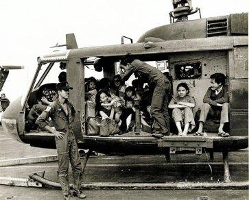 De opluchting staat te lezen op het aangezicht van piloot en vluchtelingen na de landing op het vliegdek van USS Midway