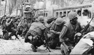 Amerikaanse mariniers zoeken dekking achter een muur tijdens de slag om Hué, februari 1968.