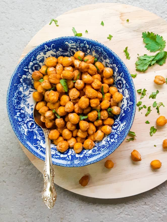 Peanut butter roasted chickpeas served in a white and blue bowl. There is a round wooden cutting board underneath the bowl