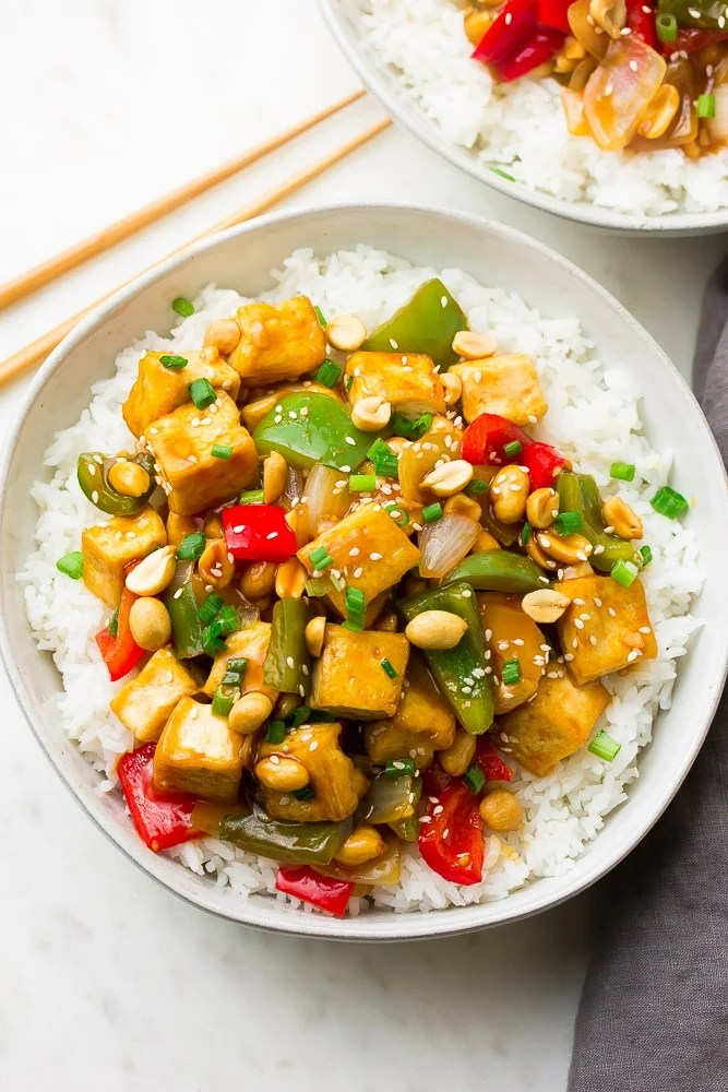 Kung pao tofu served on a bed of white rice in a white bowl