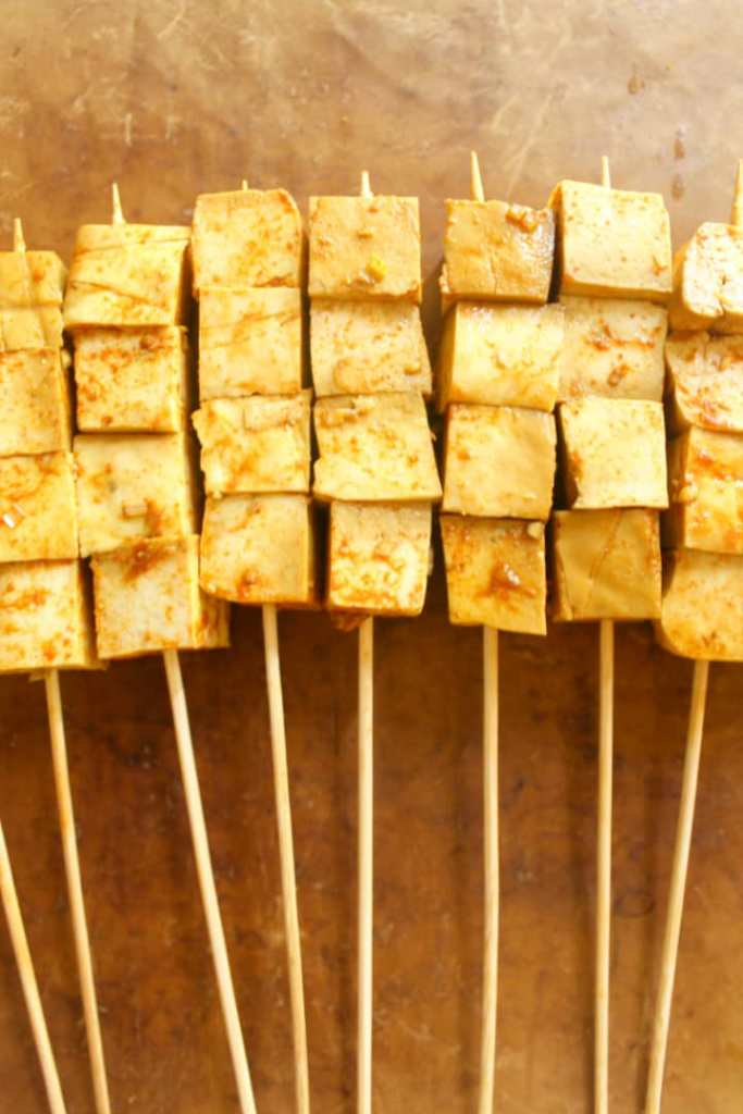 Uncooked tofu on skewers on a parchment paper